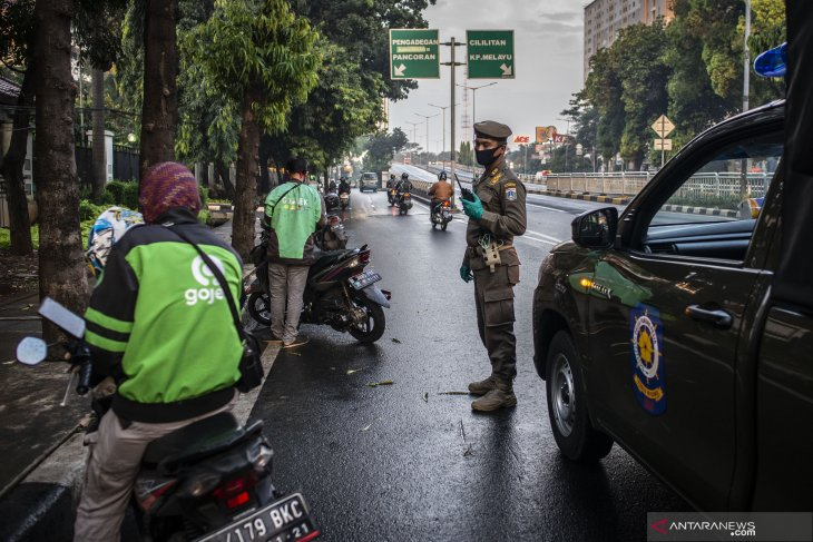 Ojek taxi driver is on the road amid Jakarta restrictions