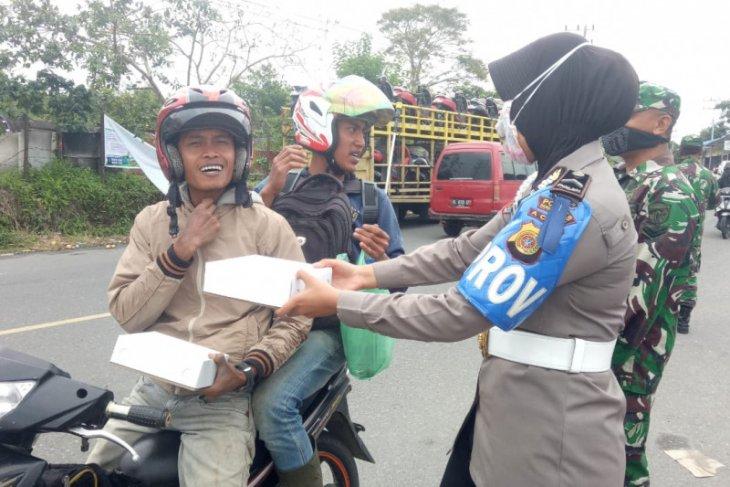 Bhayangkari Polres Bener Meriah bagi masker dan nasi kotak ke pengendara