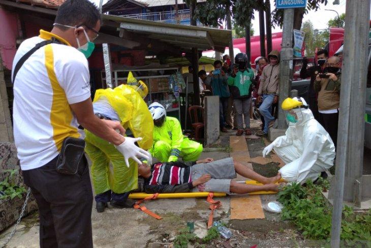 Kenakan jas hujan sebagai APD Polantas Sukabumi evakuasi warga terkapar