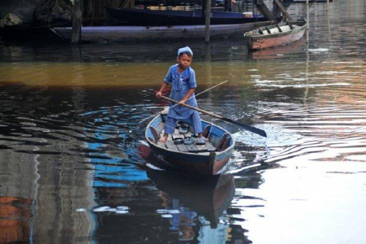 Anak berperahu menembus banjir saat Idul Fitri