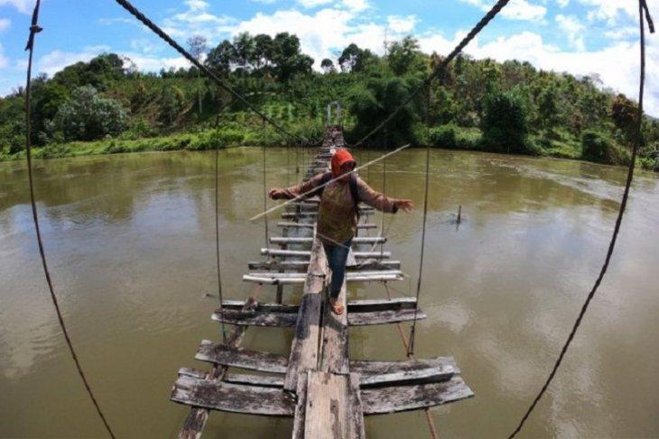 Seorang wanita  menyeberang di atas jembatan rusak di Kerinci