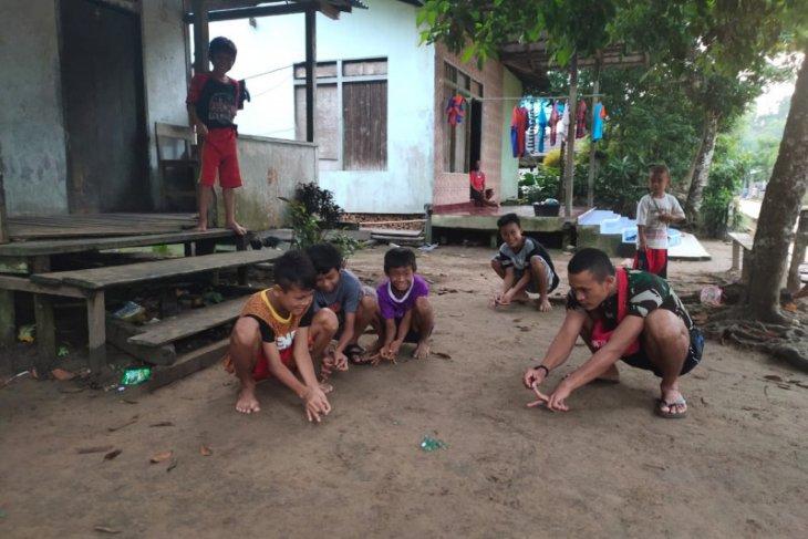 Anggota TMMD ikut bermain kelereng bersama anak-anak