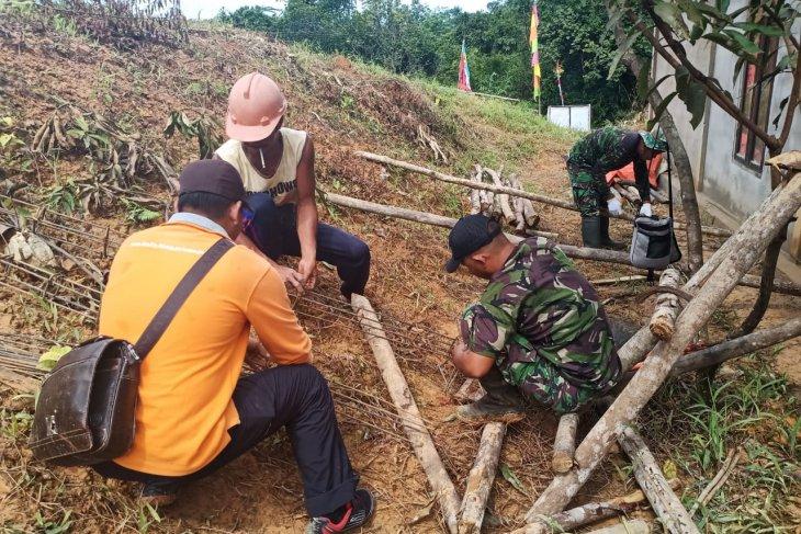 Personel Satgas TMMD bersama warga rangkai besi cor
