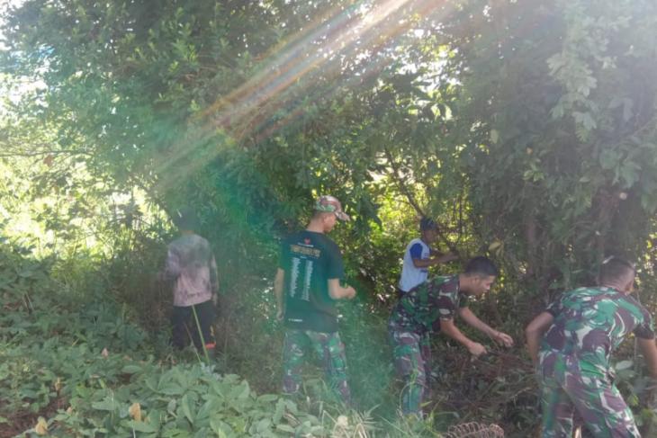 Satgas TMMD bersama warga bersihkan semak belukar dan pohon