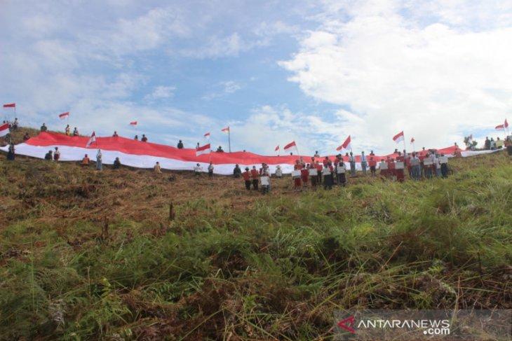 Bendera merah putih raksasa berkibar di batas Indonesia - Malaysia