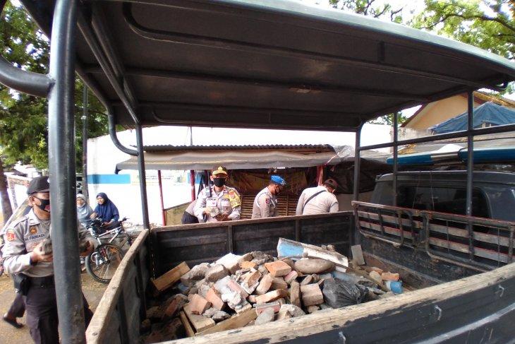 Polisi Situbondo bersihkan batu di lokasi unjuk rasa