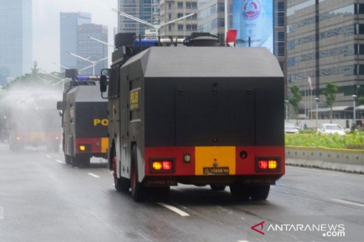 Brimob semprotkan disinfektan di ruas jalan protokol Ibu Kota