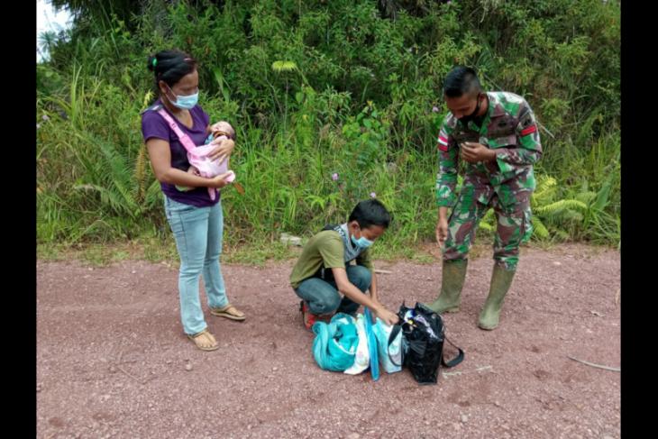 Seorang ibu membawa balita melintas jalur ilegal di batas RI-Malaysia di Badau