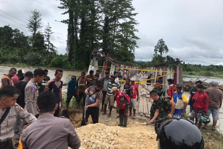 Soldiers, policemen, locals repair bridge near RI-PNG border
