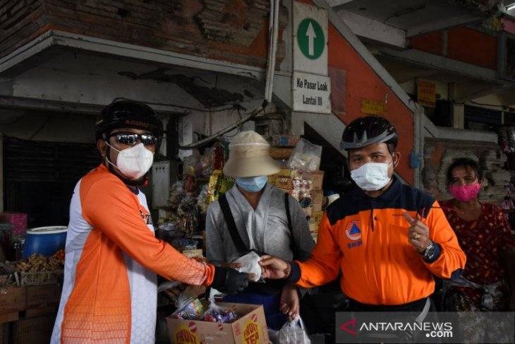 KPU Bali dan BPBD bersepeda bagikan masker ke pedagang pasar