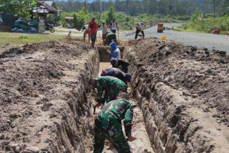 Satgas Pamtas 643/Wns bantu wargabuat drainase cegah terjadinya banjir
