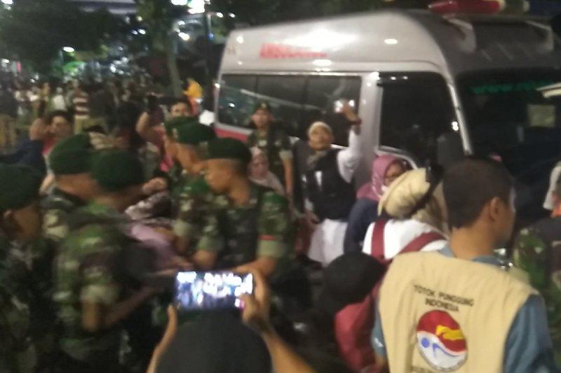 Sejumlah anggota TNI evakuasi peserta aksi yang kelelahan