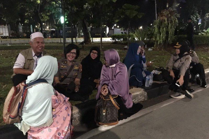 Sejumlah polwan bercakap-cakap dengan pendukung paslon Prabowo-Sandi didepan gedung MK