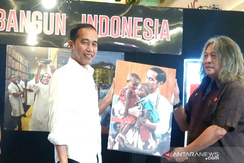 President Jokowi enchanted by his photo holding two native Papuan kids