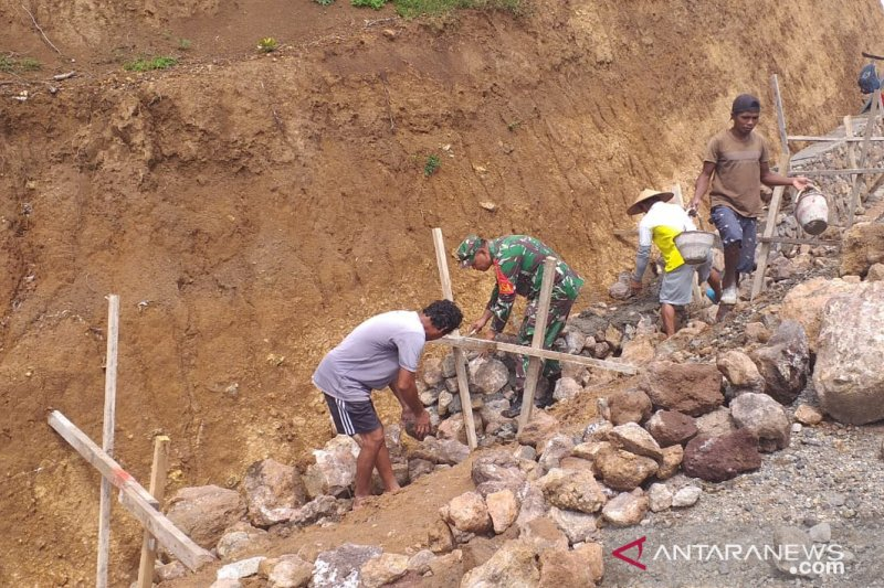Babinsa  membantu warga kepulauan Siau perbaiki drainase