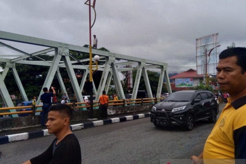 Seorang pria tak dikenal panjat jembatan Andalas