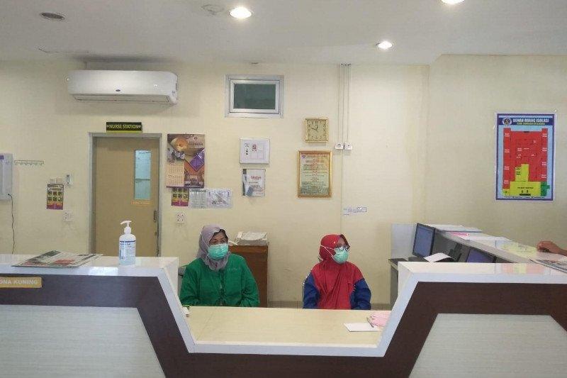 Perawat di ruang isolasi pompa semangat pasien agar sembuh