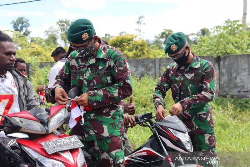 TNI pasang bendera Merah Putih di kendaraan warga yang melintasi markas