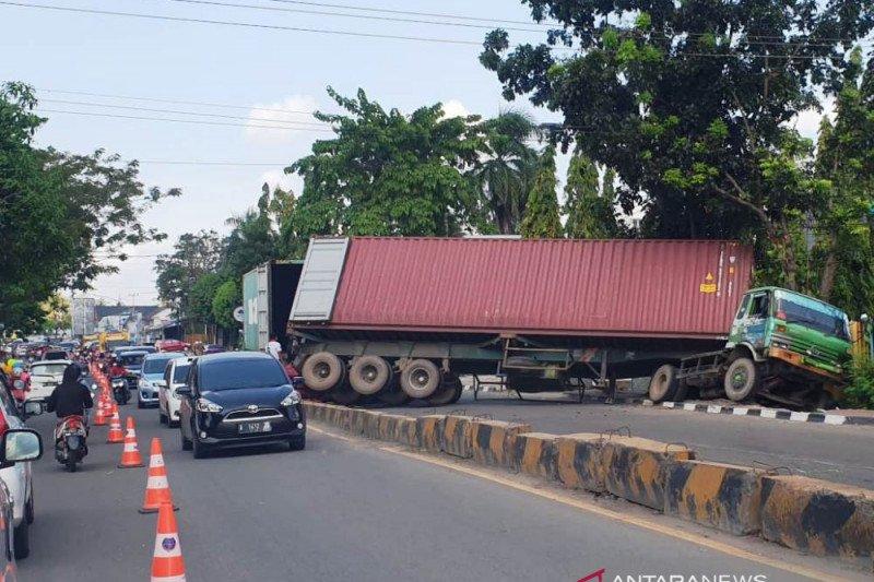 Truk peti kemas terguling di tengah jalan
