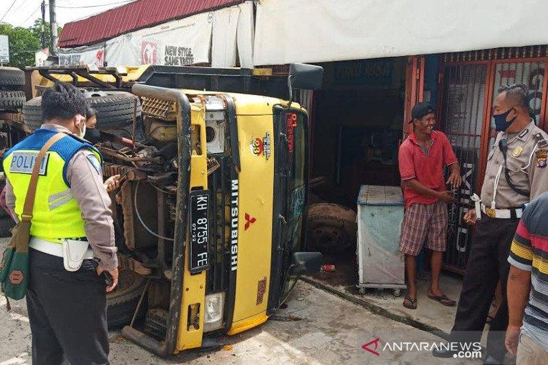 Sebuah truk terbalik usai hindari Patmor Polda Kalteng yang terjatuh