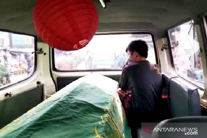 Sejumlah warga dihukum masuk ambulans berisi keranda mayat