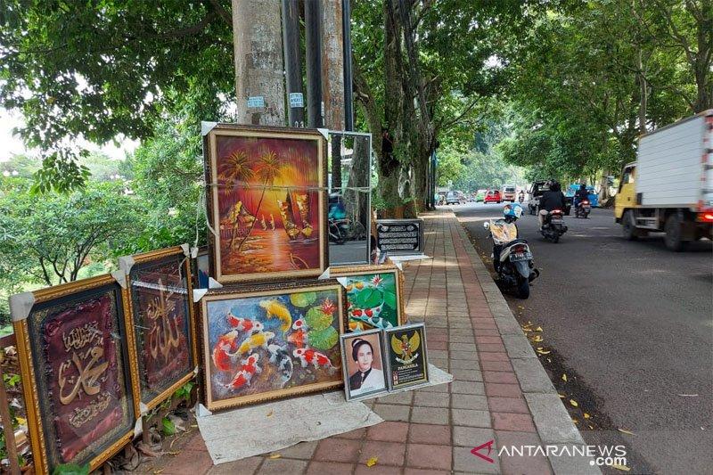 Pedagang lukisan jajakan dagangannya di Bogor Barat