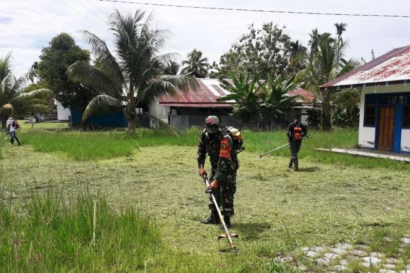 Babinsa Koramil Warbah bersihkan lingkungan perkarangan balai kampung