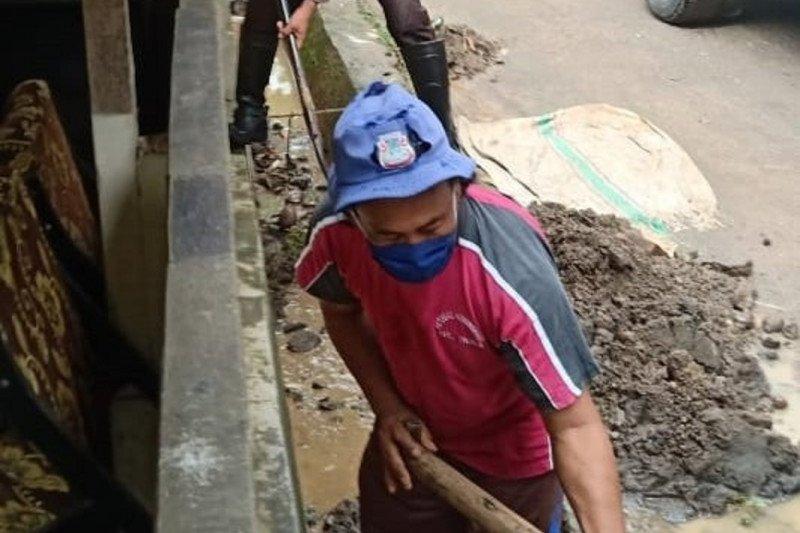 Personel Polantas Polda Sulut bantu warga bersihkan material banjir Manado